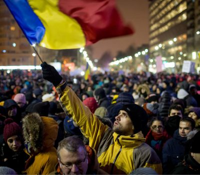 TOPSHOT - A man holds a Romanian national flag during a demonstration to protest against controversial decrees to pardon corrupt politicians and decriminalise other offences, on January 29, 2017 in Bucharest. Around 40,000 demonstrators took to the streets of Bucharest and other Romanian towns on January 29, 2017. / AFP / ANDREI PUNGOVSCHI        (Photo credit should read ANDREI PUNGOVSCHI/AFP/Getty Images)